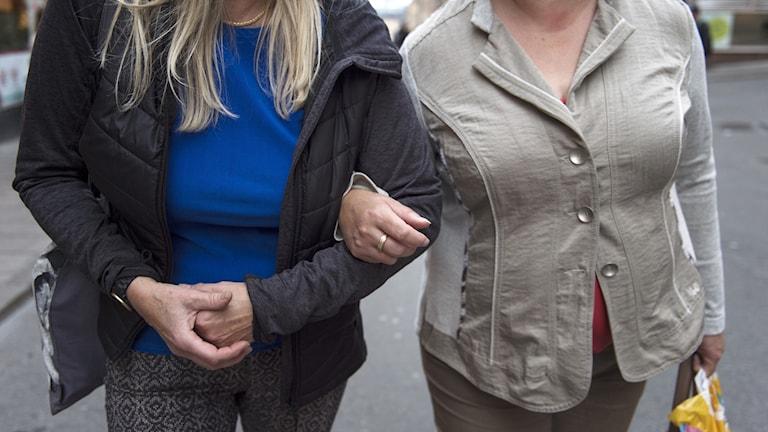 Två kvinnor som går armkrok