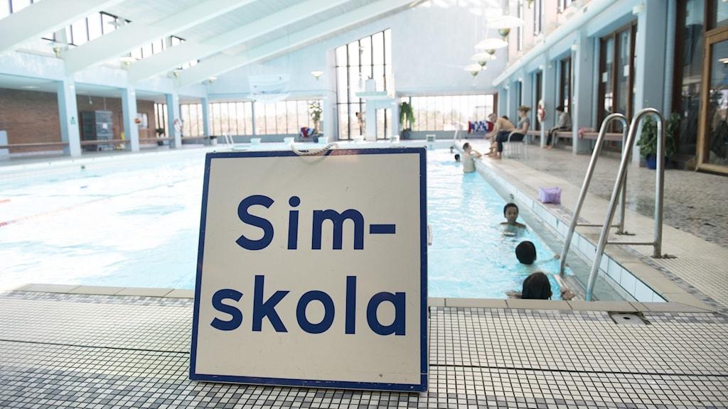 """en skylt som det står """"Simskola"""" på placerad vid kanten av en simbassäng."""