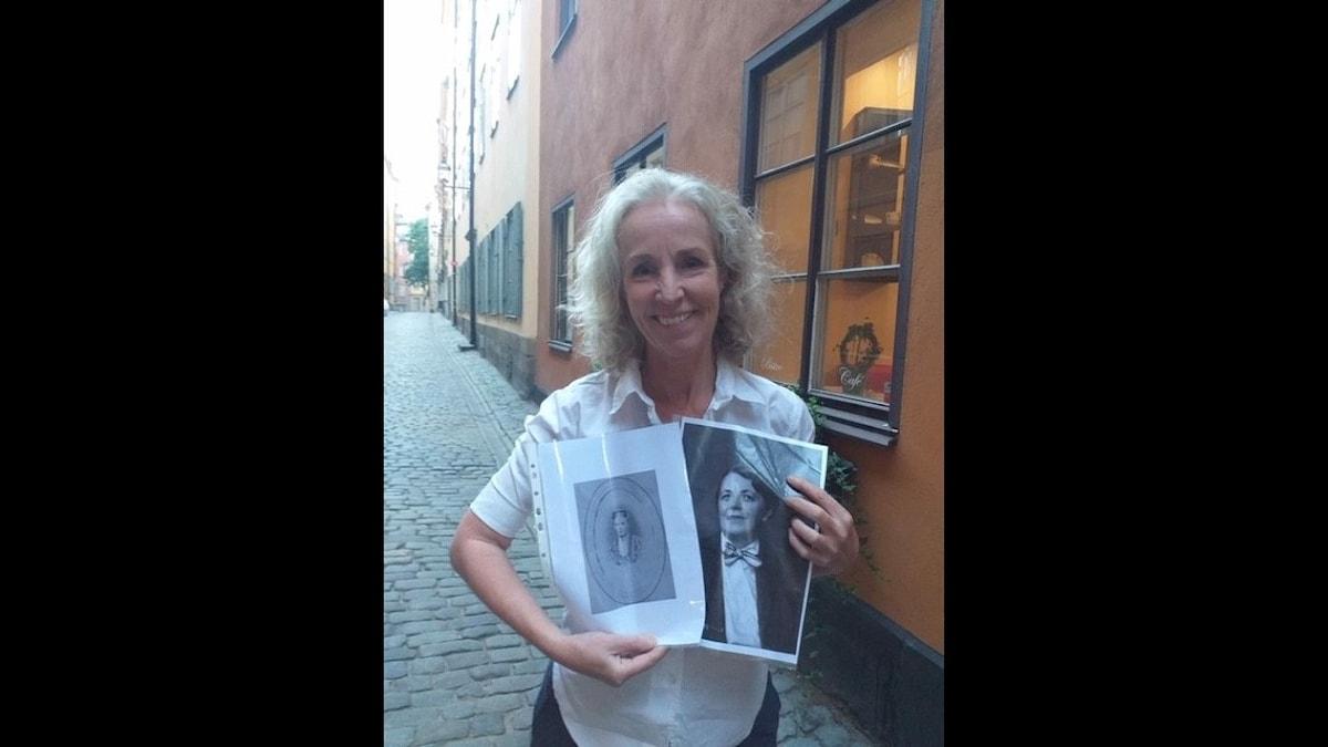 Kvinna står i Gamla stan i Stockholm på en gågata. Håller två bilder i handen.