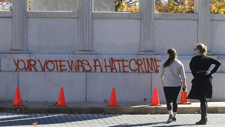 """Fotgängare i Richmond, USA, går förbi graffiti där det står """"Din röst var ett hatbrott""""."""