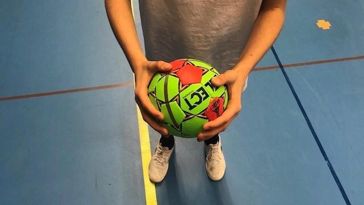 Närbild på två händer som håller i en handboll.