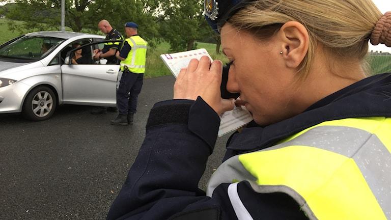 Bilderna visar sergeanten Marlies vid den nederländska militärpolisen som granskar ett pass med hjälp av förstoringsglas. I bakgrunden kontrollerar en av hennes kollegor en bil. Foto: Anna Bubenko/Sveriges Radio.