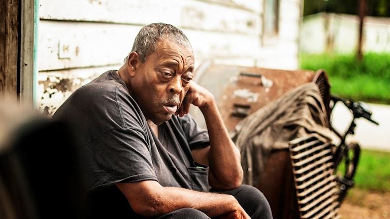 En man sitter på fastun till sitt hus. Han vilar huvudet mot sin hand och tittar ned i backen. För vissa, som Raymond Hughes, har orkanen också inneburit stölder och ökad osäkerhet.