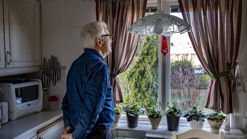 Man som tittar ut genom ett fönster