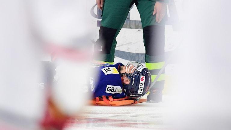 Mann ligger med hjälm på isen.