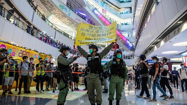 Polis håller upp en varningsflagga för demonstranter i en galleria i Hong Kong tidigare i veckan.
