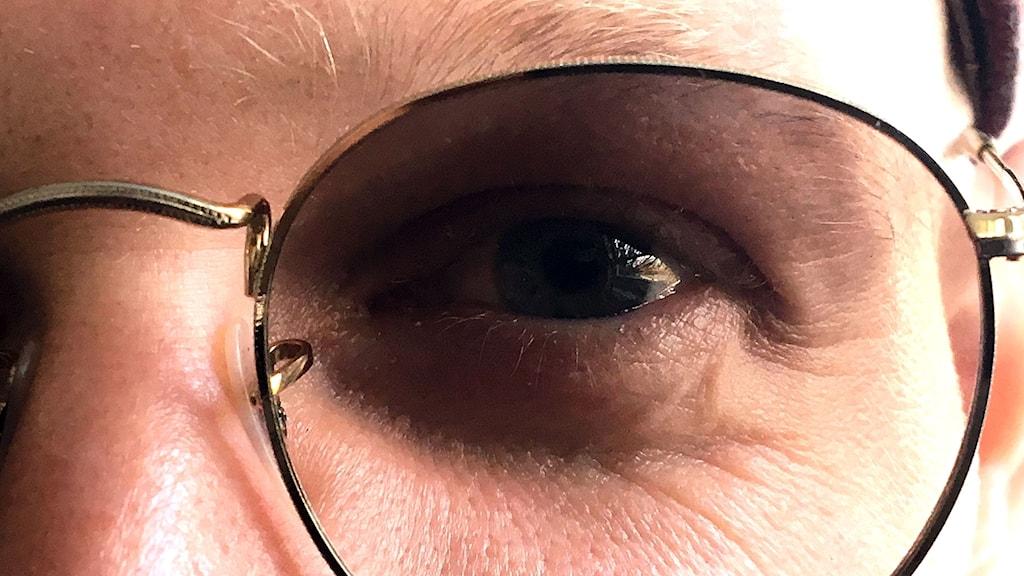 närbild på ett öga, bakom ett glasöga