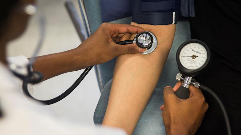 Kvinnlig läkare mäter blodtrycket på patient .
