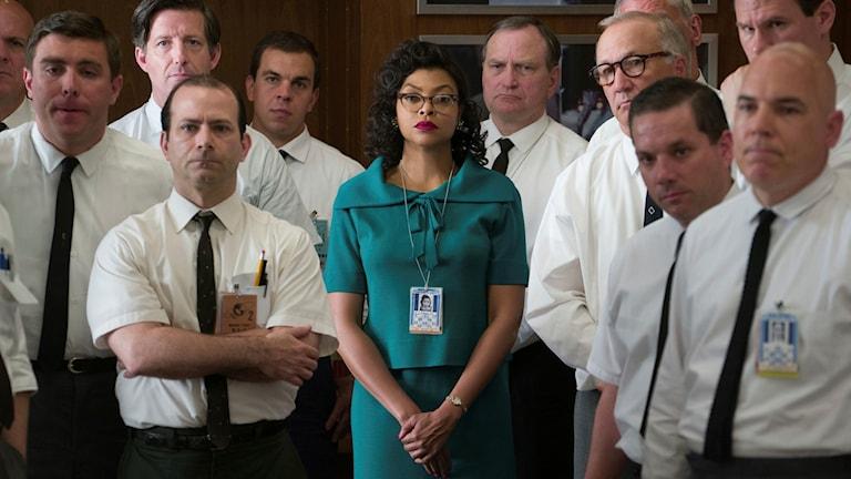 En kvinna står med flera män i bakgrunden.