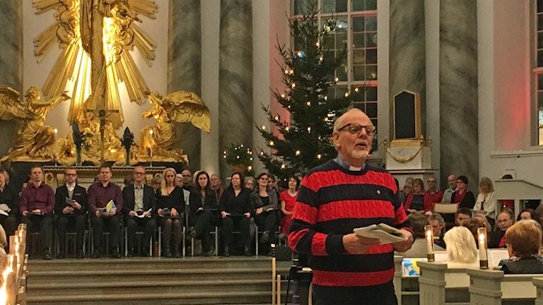 En man står framför en kör och en julgran i en kyrka.