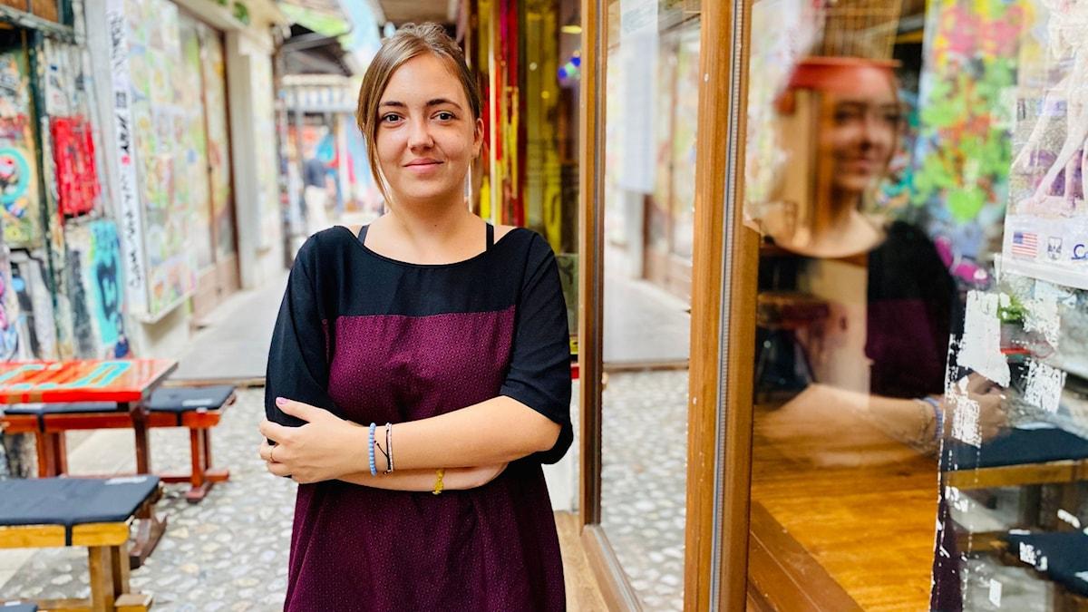 Kvinna står på en turistgågatan i Sarajevo och tittar in i kameran.