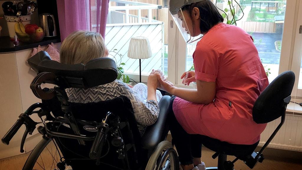 Kvinna som arbetar på demensboendet, klädd i rosa, målar naglar på boende.