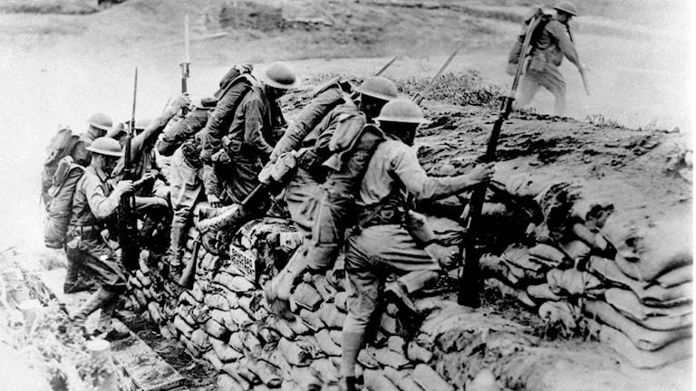 Amerikanska trupper klättrar över ett skydd gjort av sandpåsar i Frankrike under första världskriget.