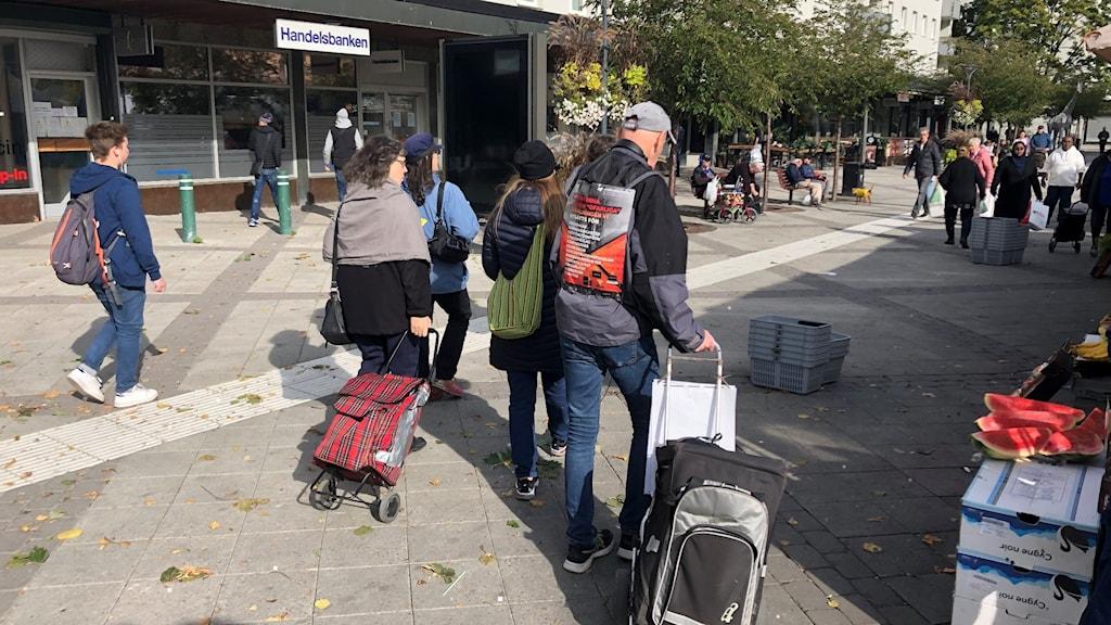 Personer som går på ett gångstråk. Två av dom drar på Dramaten-väskor.