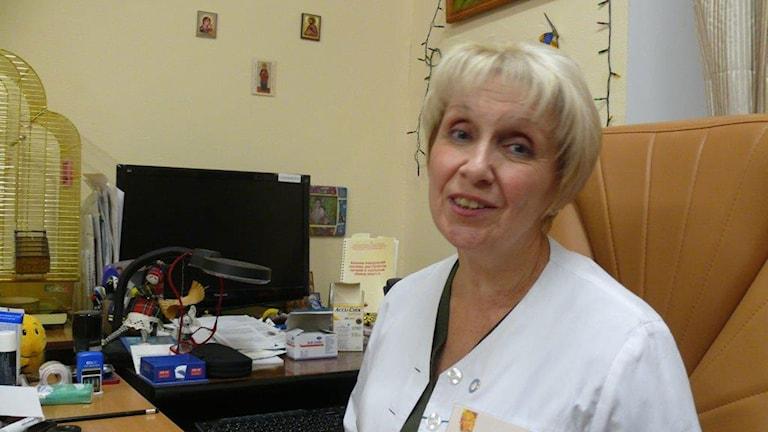 Överläkaren och endokrinologen Olga Demitjeva sitt i sin vita läkarrock vid sitt skrivbord. Foto: Maria Persson Löfgren/Sveriges Radio