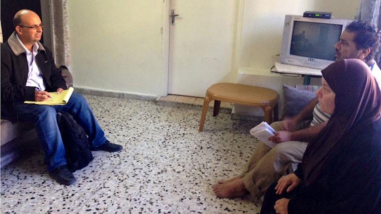 Ammar Awad pratar med två personer i ett rum. En tv syns i bakgrunden.