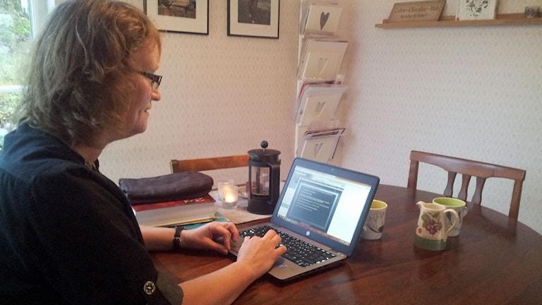 Malin Jonason, sitter vid köksbordet och försöker hitta rätt i skolans alla digitala rum. Foto: Carina Holmberg/Sveriges Radio.