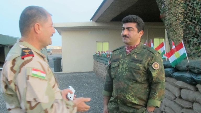 Två män pratar vid en militärbas.