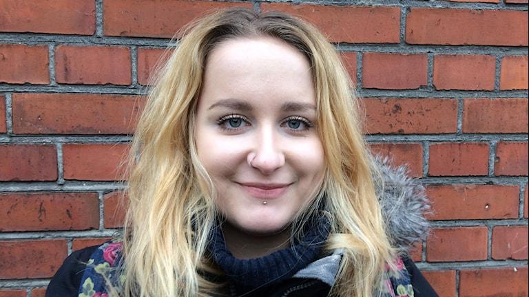 Porträttbild av Pernilla West mot en tegelvägg.