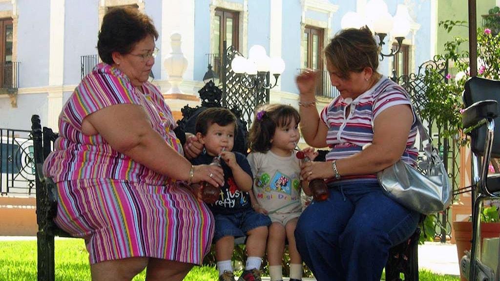 två tjocka tanter med små barn på bänk