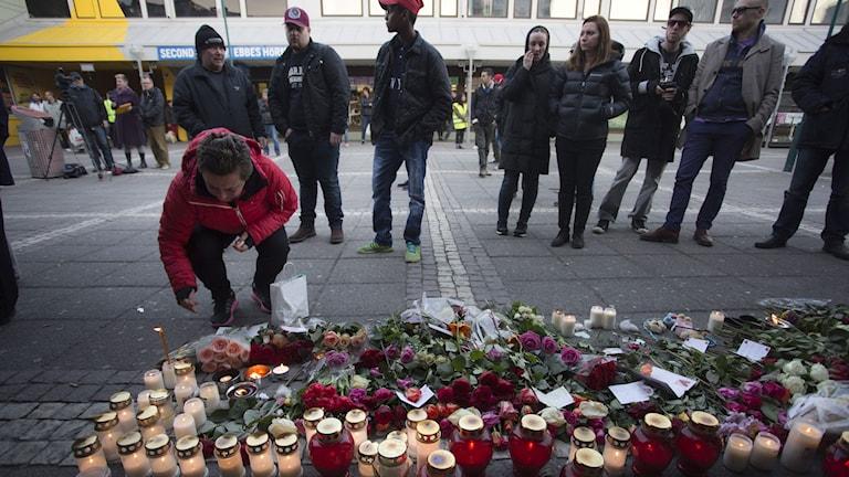 Blommor och ljus vid platsen för skottlossningen i en restaurang på Vårväderstorget på Hisingen i Göteborg. Foto: TT