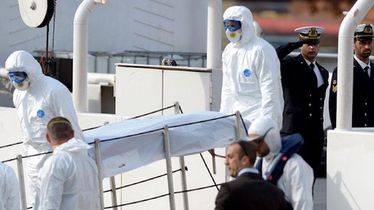 Kroppar förs i hamn på Malta. En officer vid den italienska kustbevakning gör honnör för de omkomna som lämnar fartyget. Foto: Matthew Mirabelli/AFP