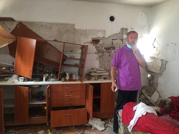 Agron Aidini visar runt i sitt sönderskjutna hus i Kumanovo. Foto: Johanna Melén/Sveriges Radio