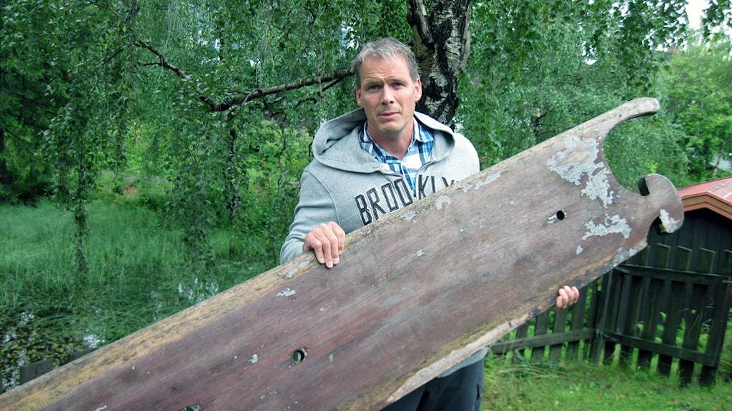 Torgeir Sæverud Higraff håller upp ett av de stora, tunga bord som används för att styra balsaflotten.