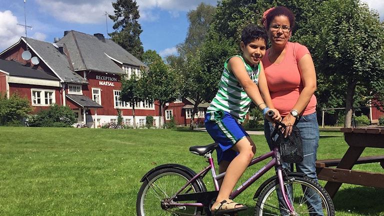 pojke på cykel och en mamma bredvid framför rödmålat asylboende