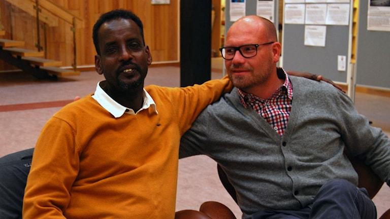två män sitter och håller om varandra på ett bibliotek.