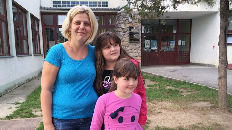 En mamma med två döttrar framför skola.