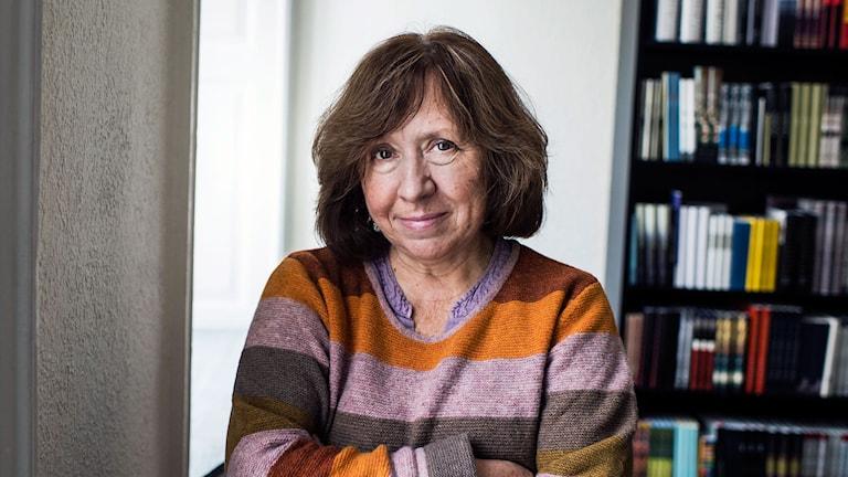 Swetlana Alexijewitsch in farbenfrohem breit gestreiften Pullover steht mit verschränkten Armen vor Bücherregal. (Foto: Vilhelm Stokstad/TT)