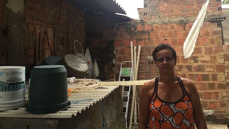 Lucia på sin innergård i Caruaru i delstaten Pernambuco. Vattnet i tanken bakom henne fylls på en gång i månaden. Foto: Lotten Collin/Sveriges Radio.