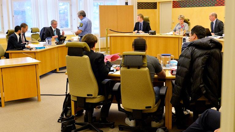Sonen till den uzbekiske imam och regemkritiker som utsattes för ett mordförsök, längst till vänster, åklagaren Christer Pettersson, tredje personen från vänster. Den åtalade mannen i mitten tillsammans med sin försvarsadvokat till höger och en tolk till vänster i tingsrätten i Östersund. Foto: Marcus Ericsson / TT