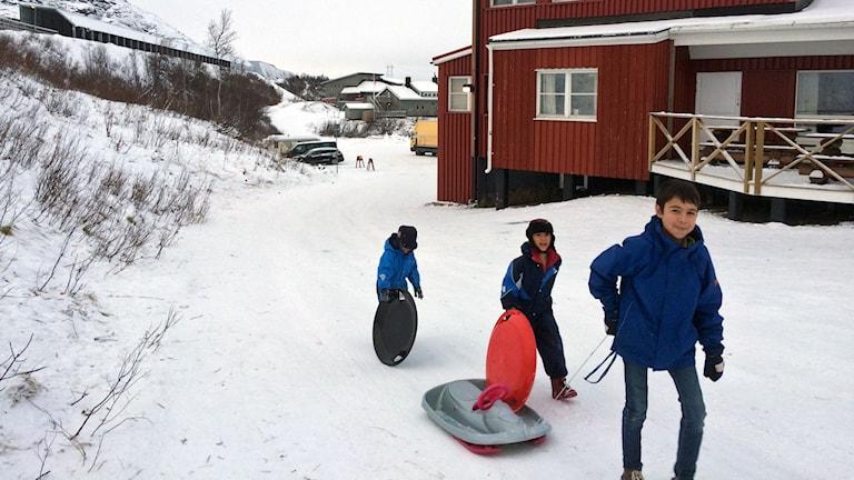 Tre barn med pulka och tefat i vinterlandskap framför rött hus.