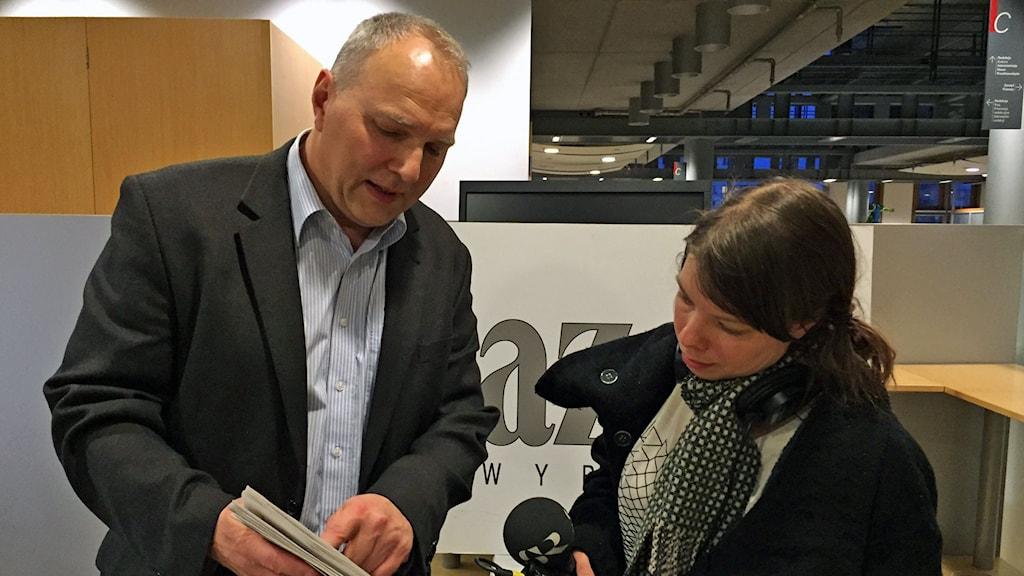 man i kostym pekar i tidning bredvid radioreporter Foto: Sveriges Radio