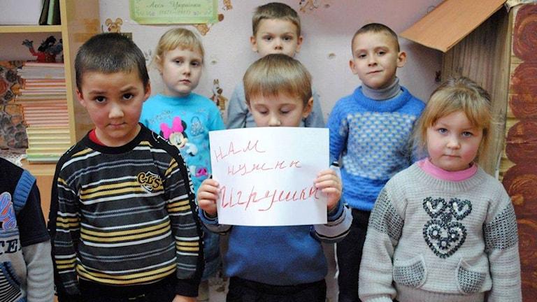 Några av barnen som Ukrainska Volonterska, en av de frivilligorganisationer som får stöd från Sverige, hjälper. På skylten står: Vi behöver leksaker. Foto: Maria Persson Löfgren/Sveriges Radio