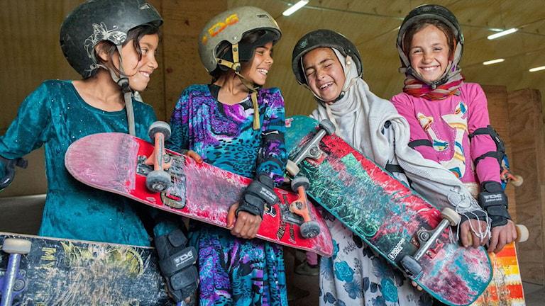 Fyra afghanska flickor som lärt sig åka skateboard. Foto: Skateistan
