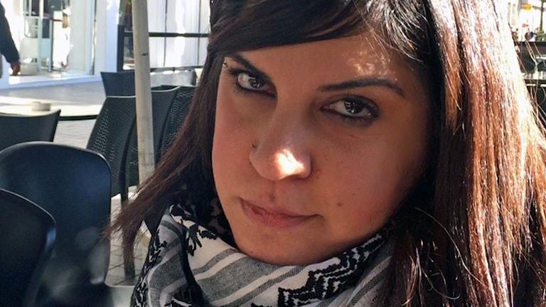 närbild på kvinna klädd i svart/vit palestinasjal i utomhusmiljö