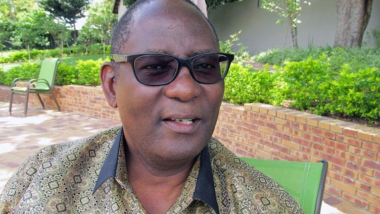 närbild på sydafrikansk man i svarta glasögon, parkmiljö