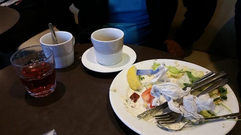 Glas, kaffekoppar och matrester på tallrik står på ett brunt bord