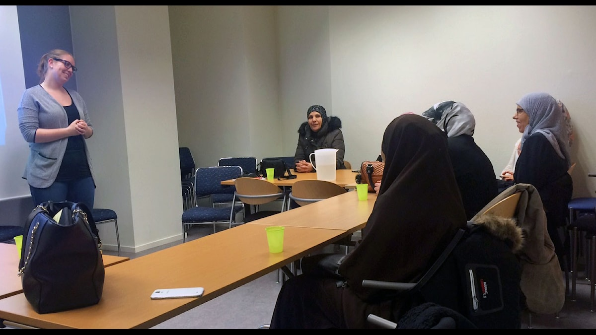 kvinnor klädda i huvudduk sittandes i lektionsrum, lärare står framför.