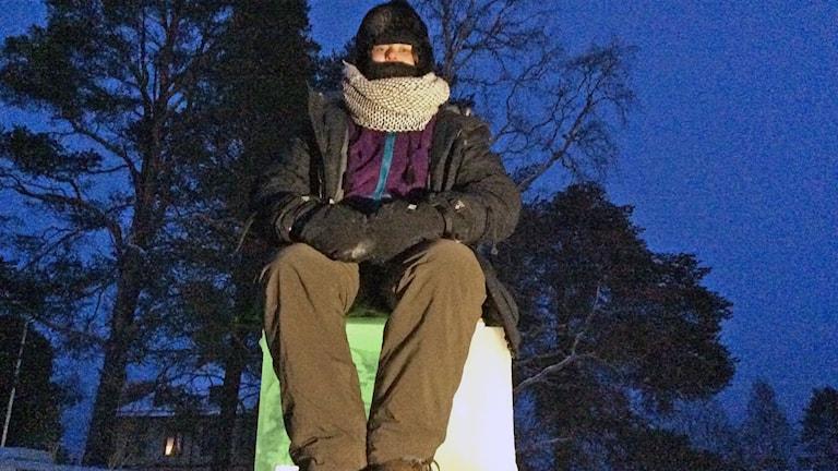 kvinna sitter påklädd till tänderna på en isstolpe i Vilhelmina