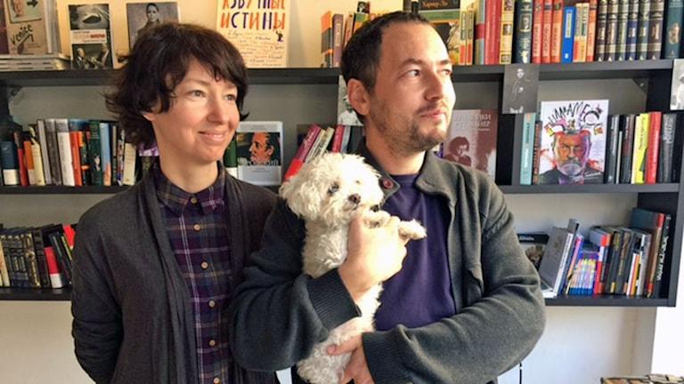 intriör bokhandel; en kvinna, en man och en hund