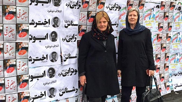 Cecilia Uddén och Agneta Ramberg framför väg med valaffischer i Iran