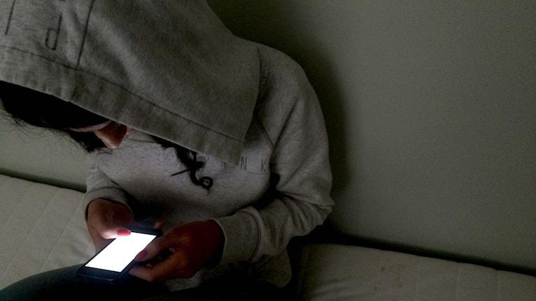Flicka med huvtröja ser ner i mobiltelefon. Foto: Marcus Eriksson/Sveriges Radio.