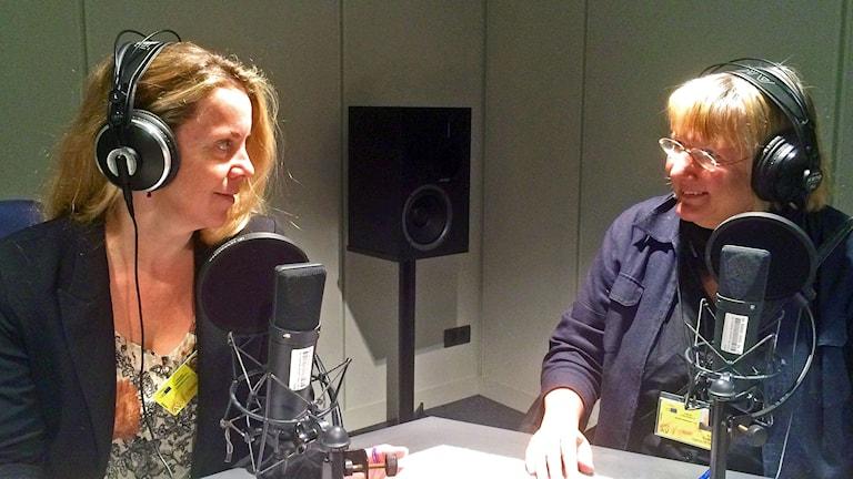 Två kvinnor tittar vänligt mot varandra i en radiostudio