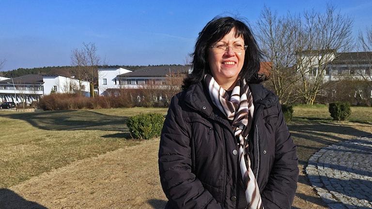 kvinna i mörkt hår och täckjacka, utomhus miljö, låga hus i bakgrunden
