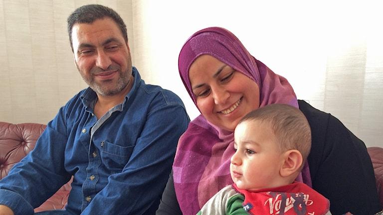 Turkl Alkhezam och Ludinah Alrefaei sitter i soffan med sitt yngsta barn. Foto: Laila Carlsson/Sveriges Radio