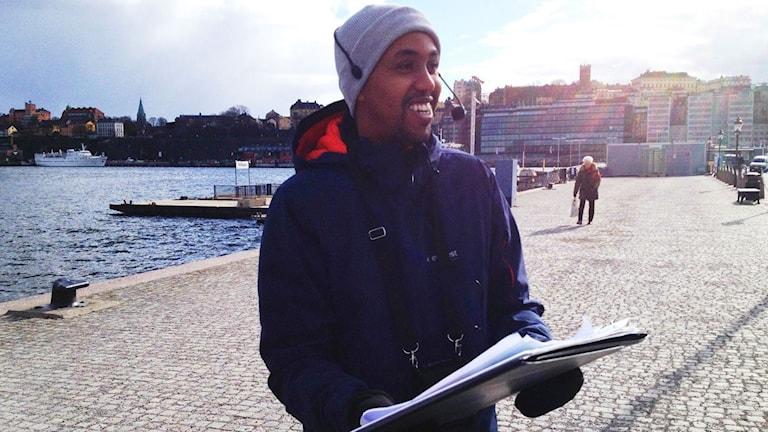 En guide med headset och papper i handen står på en kaj.